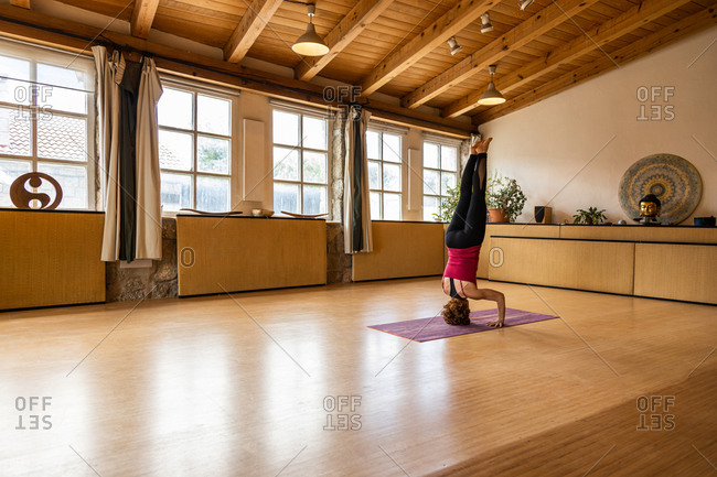 Full body side view of unrecognizable female in sportswear doing Free Hand Headstand while practicing yoga alone in spacious yoga studio with natural interior