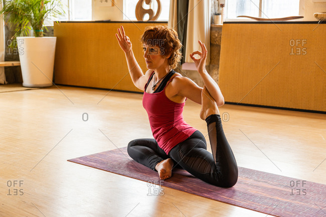 Full body of focused middle aged female in sportswear sitting in King Pigeon asana with mudra gesture while practicing meditation during Shakti yoga session in studio