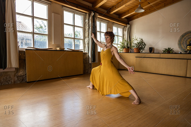 Side view of focused female standing barefoot in studio in Anjaneyasana and doing yoga while looking up