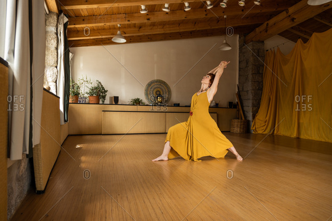 Side view of concentrated female in long waving dress standing barefoot in studio and practicing yoga in Anjaneyasana