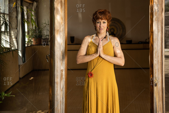 Serene female standing in doorway in courtyard and doing mountain pose while practicing yoga looking at camera