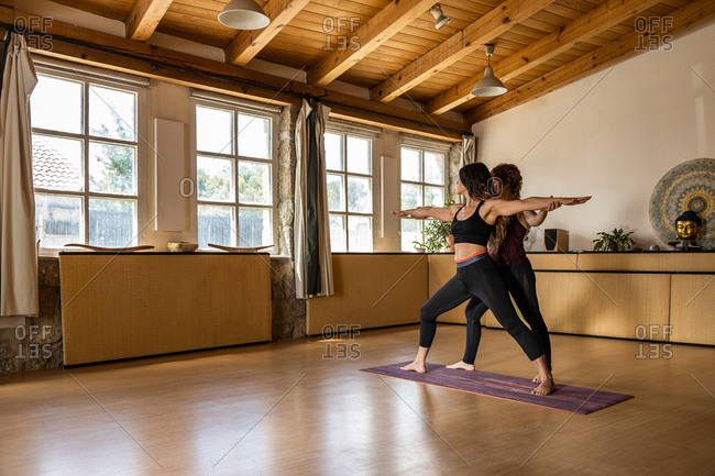 Flexible woman standing in Warrior pose and practicing yoga with help of female trainer in spacious studio