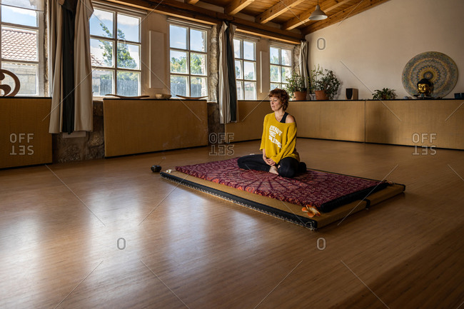 Calm female in sportswear sitting on mat in spacious studio and practicing yoga in Padmasana meditation