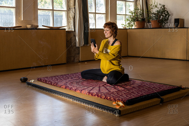 Content female sitting on mat in studio and browsing smartphone while relaxing during yoga lesson