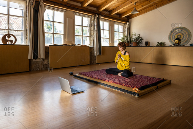 Calm female in sportswear sitting on mat in spacious studio and practicing yoga in Padmasana while filming an online tutorial on laptop