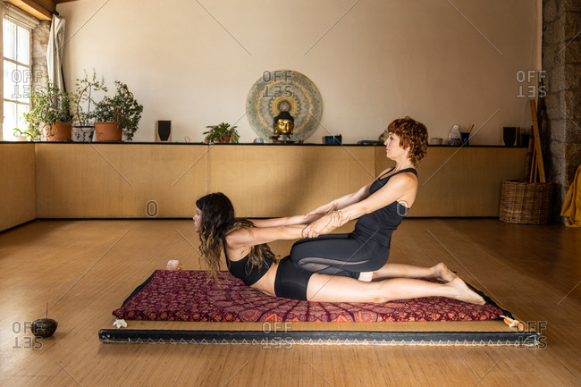 Side view of flexible females in sportswear in Cobra and Chair poses holding hands and doing acro yoga in studio