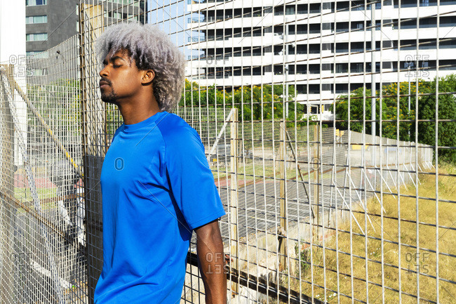 Tranquil African American male with Afro hairstyle leaning on metal grid in city on sunny day