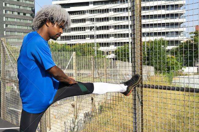 African American sportsman with blond hair standing near net fence and doing stretch during fitness workout on sunny day on city street looking away