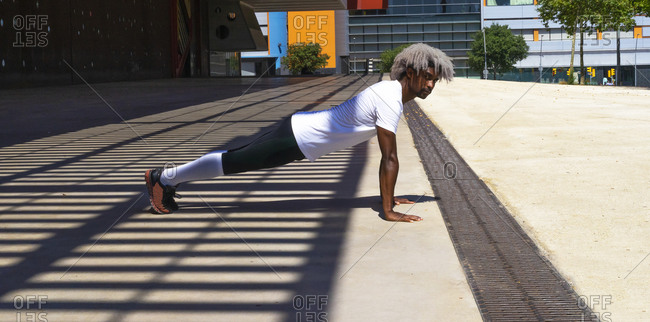 Side view of black athlete with blond hair doing push ups in enclosure during fitness workout in city