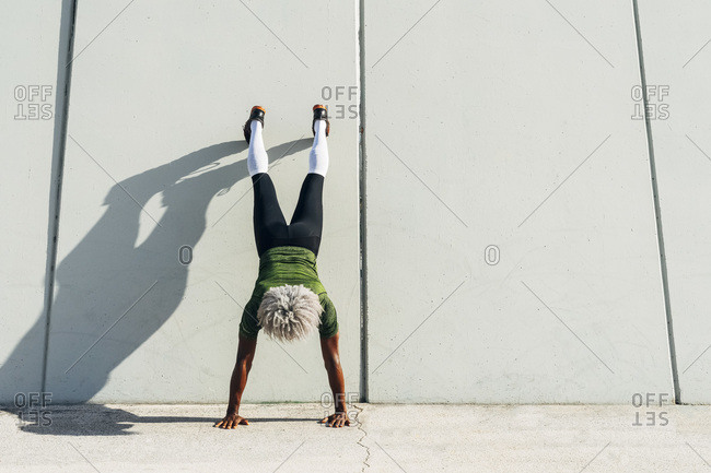 Back view of unrecognizable black sportsman with blond hair doing handstand near wall of modern building in city