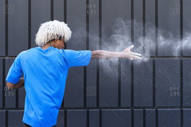 Back view of black sportsman with dyed hair throwing chalk powder in air during workout against wall of modern building