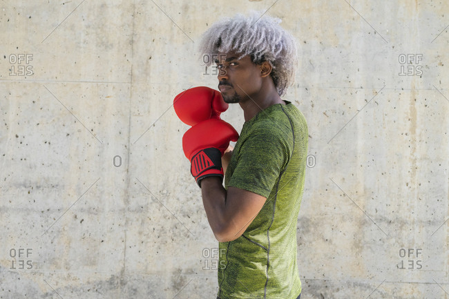 Side view of black sportsman in boxing gloves standing in guard stance and looking at camera during workout against shabby wall