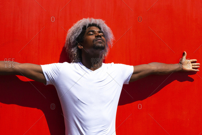 African American male athlete with outstretched arms and closed eyes resting against bright red wall on city street