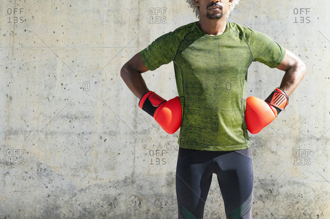 Cropped unrecognizable African American sportsman in boxing gloves standing with hands on hips against weathered wall during workout on street