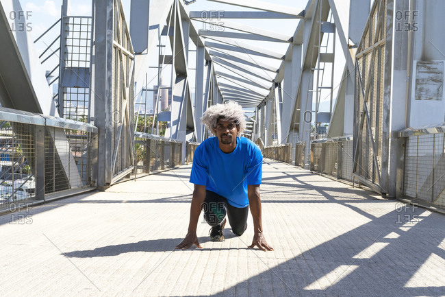 Black athlete with blond hair taking crouch start position before sprinting on modern bridge on sunny day in city