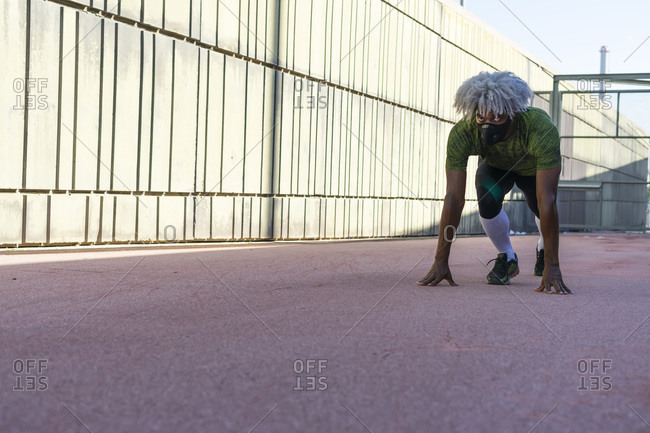 Serious black athlete with blond hair wearing a protective mask taking crouch start position before sprinting on modern concrete wall on sunny day in city