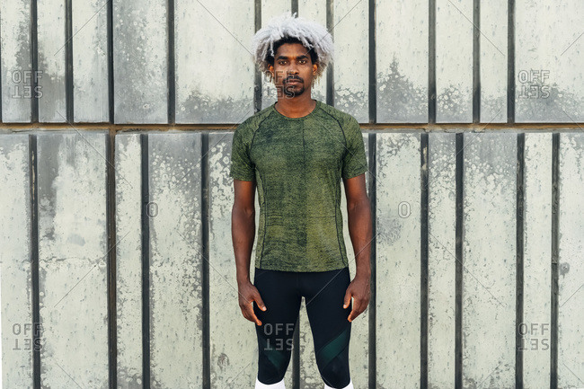 Serious ethnic sportsman with dyed hair looking at camera while standing against grungy building wall during fitness training