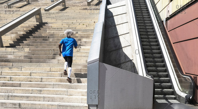 Back view of anonymous African American athlete in sportswear running up stairway of modern building near escalator during fitness workout in city