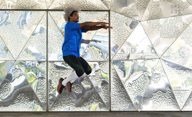 Full body powerful black athlete jumping with outstretched arms against reflective metal wall with geometric ornament during training on city street