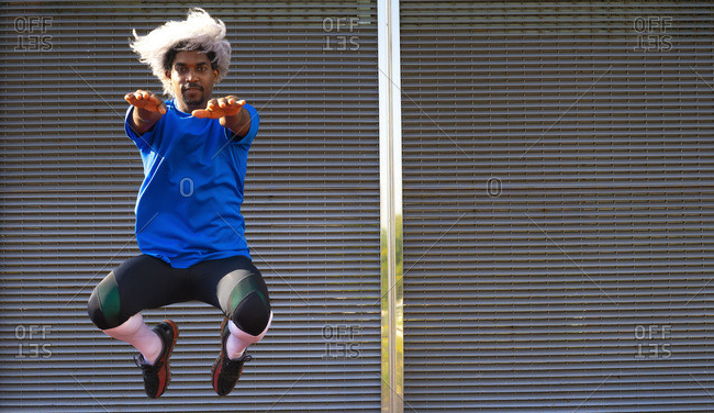 Full body black sportsman leaping up with outstretched arms and looking at camera during fitness training against wall in city