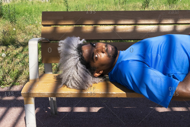 African American sportsman with dyed hair lying on bench and looking at camera during fitness training in park