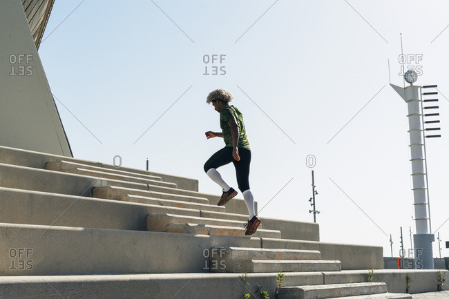 Back view of African American athlete in sportswear running up stairway of modern building during fitness workout in city