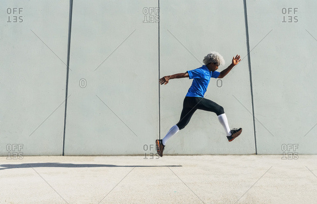 Full body side view of black athlete in sportswear leaping near modern building during fitness workout on sunny day on city street