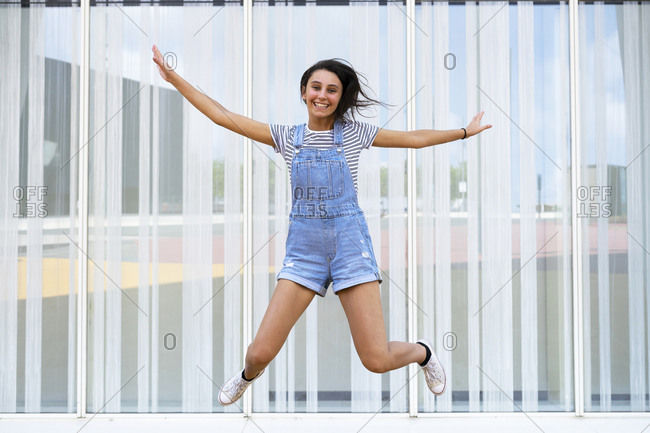 Full length cheerful teenager smiling and gesturing while leaping up near glass wall looking at camera