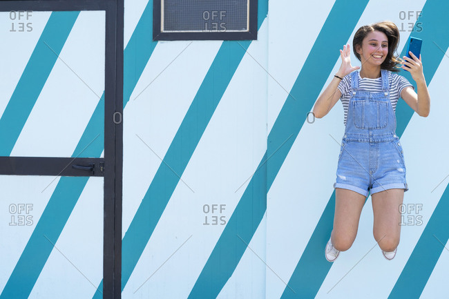 Full length cheerful teenager smiling and gesturing while leaping up and taking selfie against striped wall