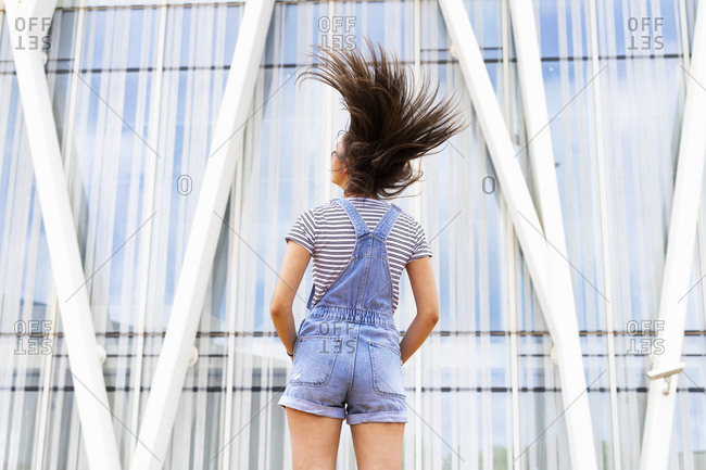 Back view of unrecognizable teen girl in casual outfit shaking long hair near modern building on city street