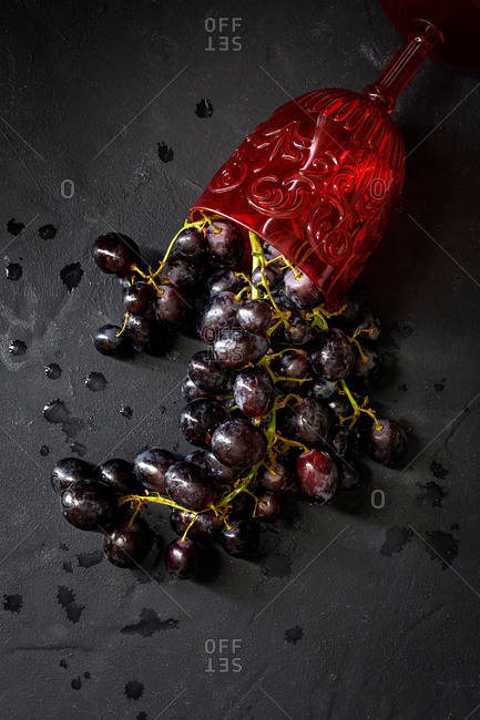 Top view of ripe juicy red grapes spilled from red wine goblet on black slate board