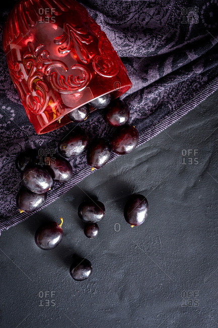 From above composition with fallen red ornamental wineglass and spilled ripe grapes on dark tablecloth