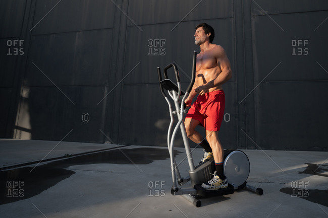 Low angle of muscular male athlete with naked torso doing exercises on elliptical stepper during training in city