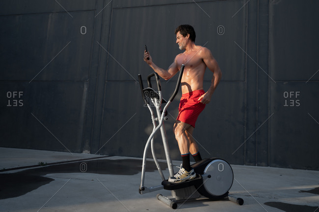 Side view of athletic male with naked torso doing exercises on stepper and taking selfie on smartphone during workout in yard