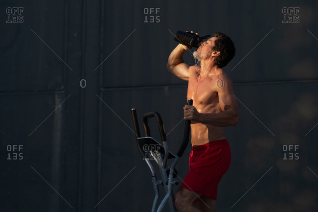 Side view of sweaty shirtless male athlete pouring water on body during intense workout on stepper