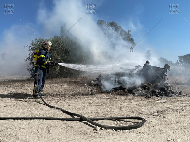 Side view of brave fireman in protective uniform standing with hose and extinguishing fire on dump in nature