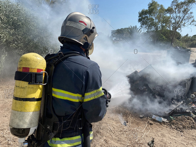 Back view of brave fireman in protective uniform standing with hose and extinguishing fire on dump in nature