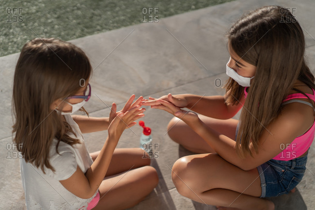 From above side view of little girls in protective masks disinfecting hands with sanitizer while sitting on paved ground in sunny summer day