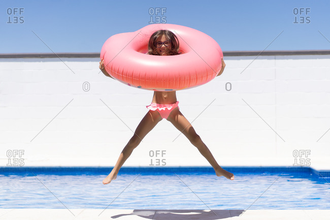 Excited girl with pink inflatable ring enjoying summer day in swimming pool during holidays