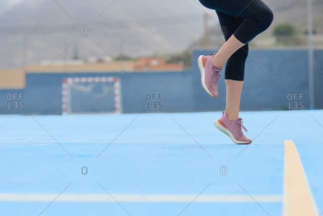 Side view of crop active female in sports leggings and sneakers performing jump exercises while warming up before running on sports ground