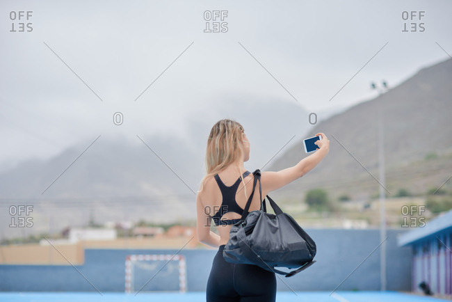 Back view of unrecognizable slim female in sportswear with sports bag over shoulder standing on sports ground and taking selfie on mobile phone after training in summer day