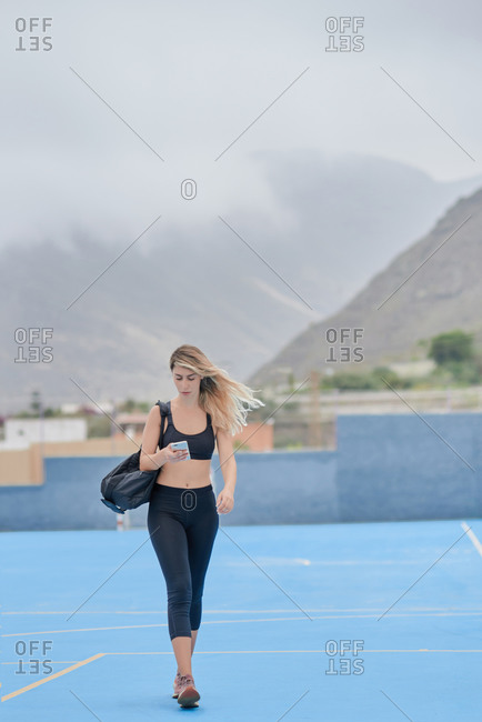 Full body side view of happy young slim sportswoman in black activewear with bag over shoulder standing on sports ground and messaging on mobile phone