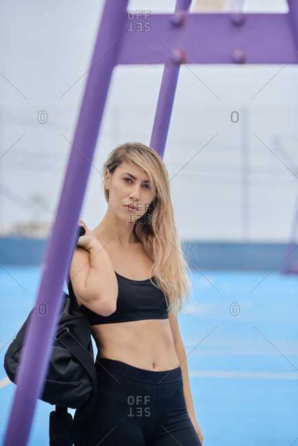 Serious young slim female in black top and leggings holding sports bag over shoulder and looking at camera while standing on sports ground