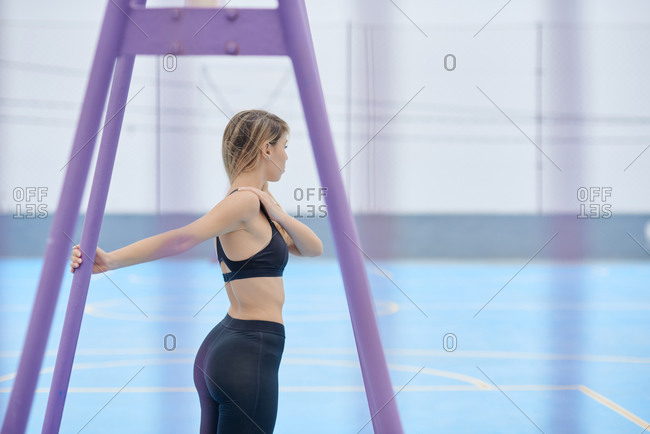 Side view of young active female in fitness top and leggings standing near metal support and stretching arms during training on sports ground