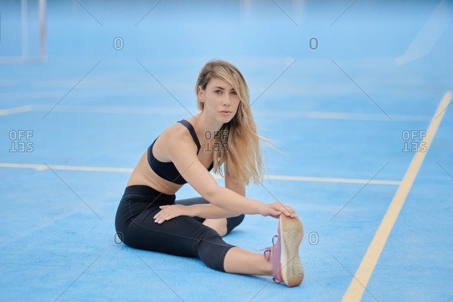 Full body of focused young fit female in sportswear sitting on blue ground and bending forward while stretching body during fitness workout on sports ground