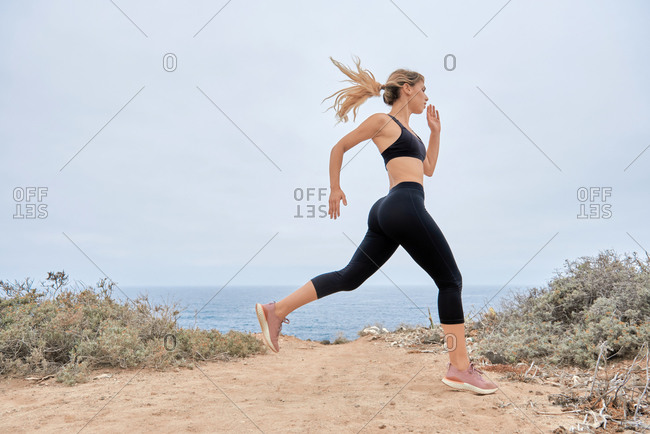 Low angle side view of young fit female in sports bra and leggings running fast along sandy seashore during fitness workout in summer day