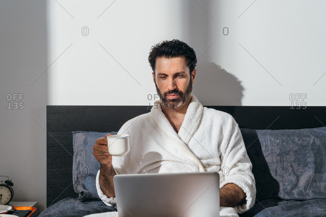 Handsome male freelancer in bathrobe sitting on bed with breakfast and cup of fresh coffee while working on laptop in morning