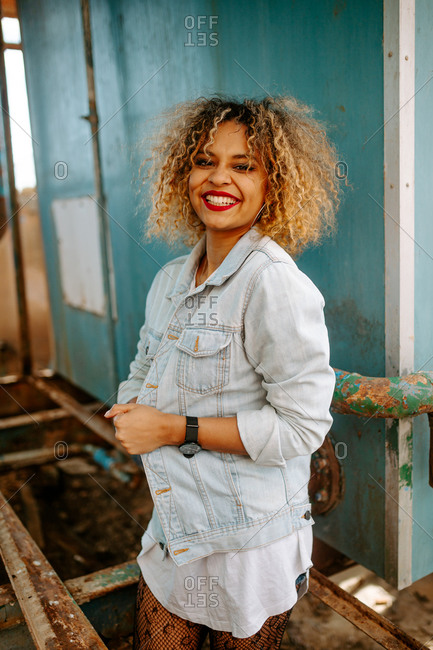 Funky African American female millennial in denim clothes standing in weathered house and looking at camera