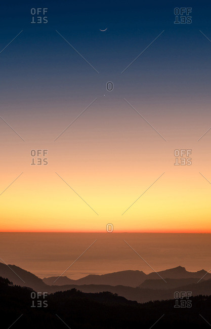 Amazing scenery of mountain range on background of spectacular orange sundown in summer in Gran Canaria