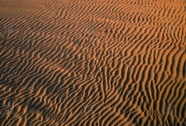 From above of textured background of rippling sand dunes in desert during sunset in Gran Canaria